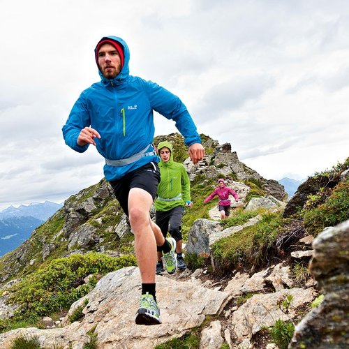 A group of joggers running a mountain trail